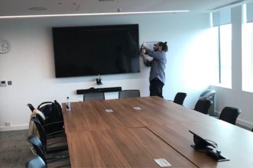AV engineer installing audiovisual equipment in meeting room