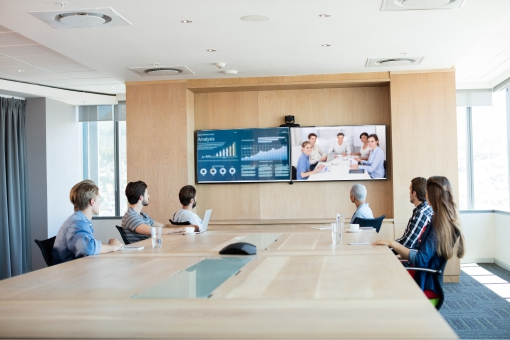 Team on a video conference call in a boardroom viewing two screens