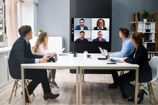 Team in a meeting room on a vide oconference call with remote workers
