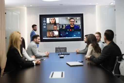 Hybrid working - colleagues talking to remote workers in a video conference